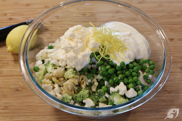 When thoroughly drained, place the pasta in a large bowl, add the broccoli, cauliflower, peas, prepared ranch dressing, mayonnaise, and lemon zest.
