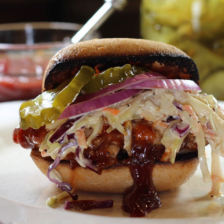 BBQ Chicken Sandwich on a plate with sauce and pickles in background