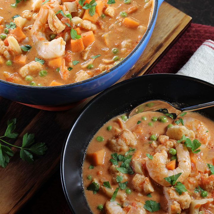 Berbere Shrimp Curry shown in a bowl nect to a pot of the stew