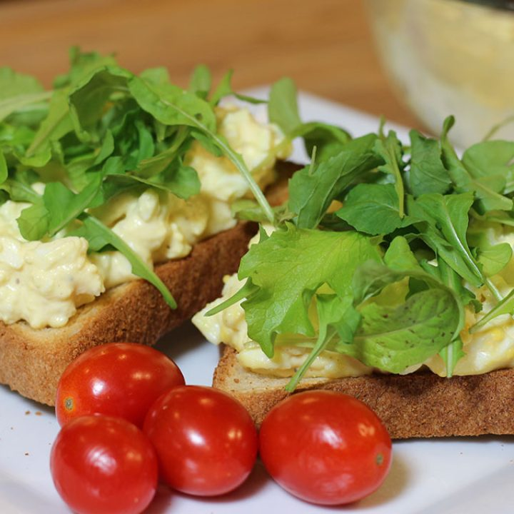 Egg salad spread on toast with baby lettuce and microgreens, served on a plate with grape tomatoes.