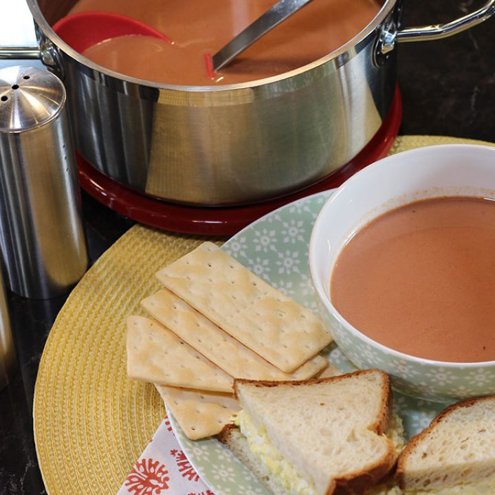 Bowl of homemade tomato juice on a plate with crackers and an egg salad sandwich with a pan of soup in the background