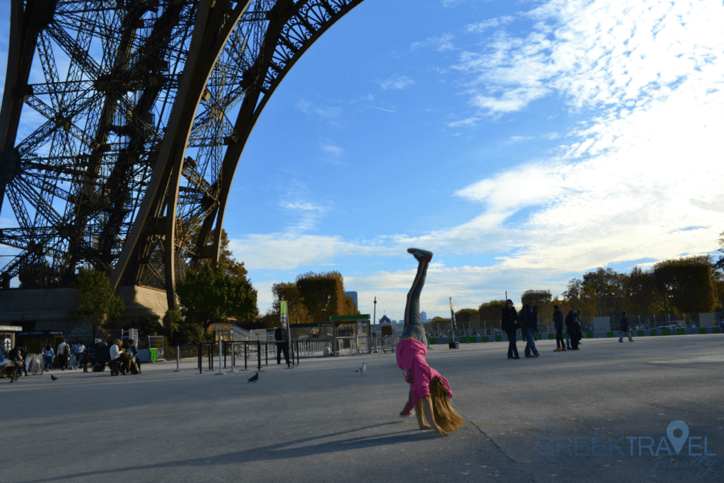 Under the arches of the Eiffel Tower in Paris. Travelling with kids.