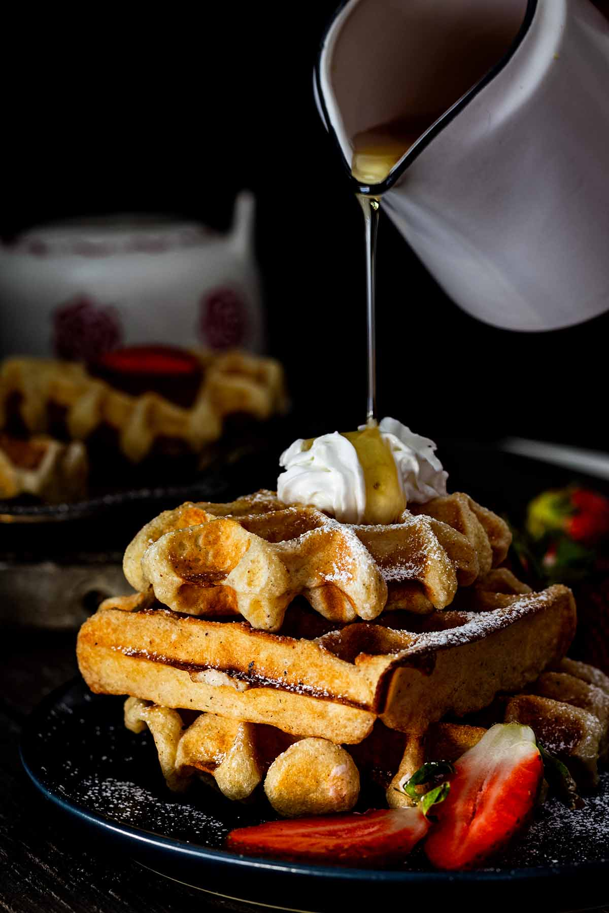 Syrup being poured onto a stack of buttermilk Belgian waffles