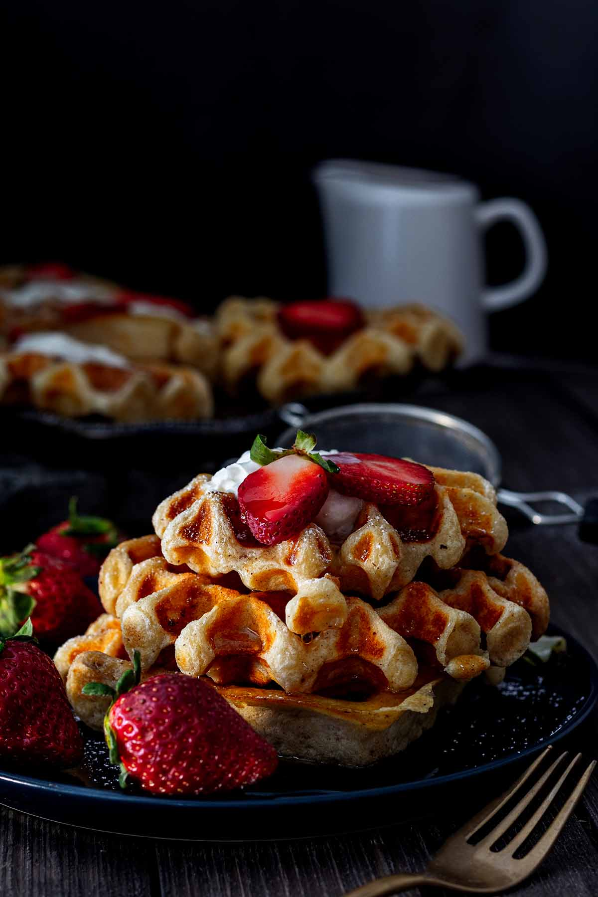 Stack of waffles on a blue plate with strawberries