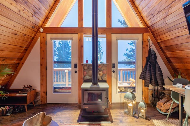 Interior of a frame cabin with wood burning stove and view