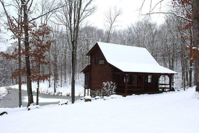 snow covered romantic cabin with a pond behind