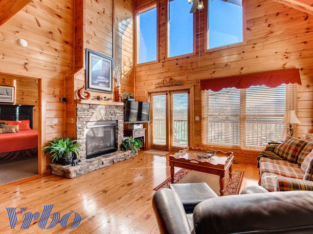 cabin living room with large fireplace and views out the window