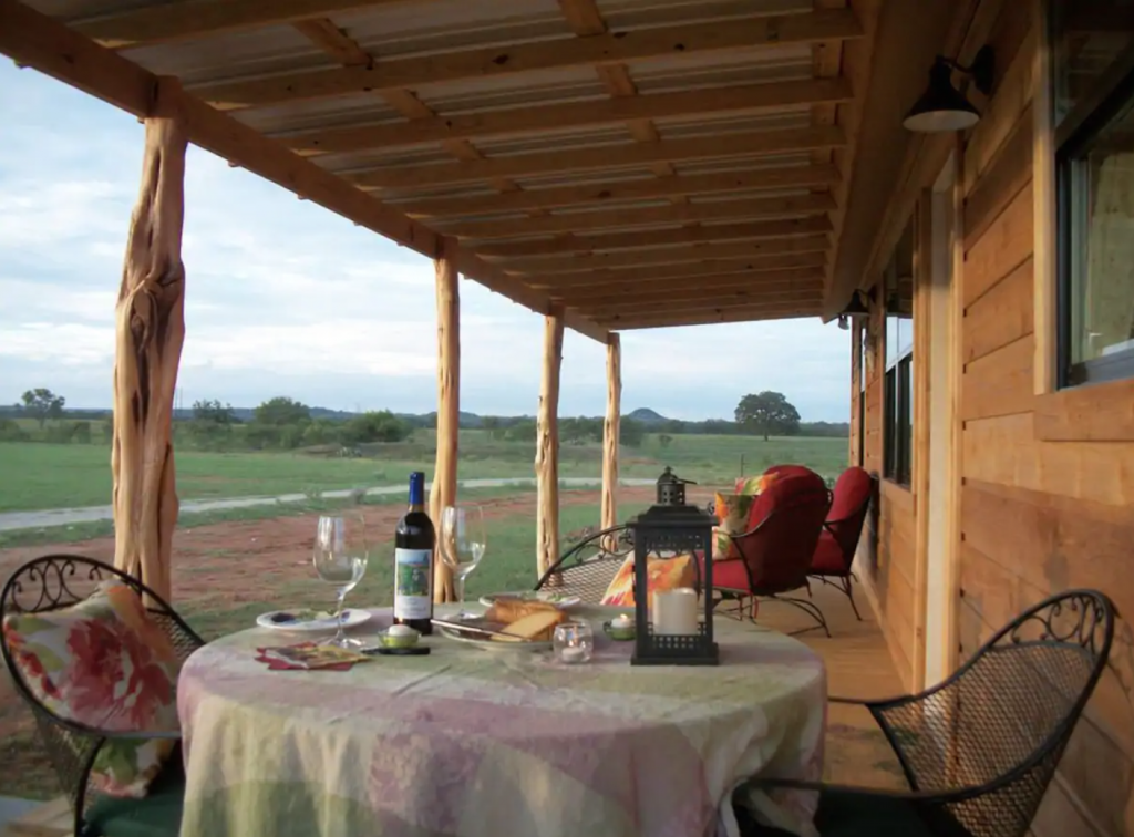 Cabin front porch with romantic table set for wine and cheese