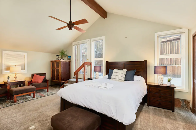 master bedroom in cabin with door to patio and hot tub