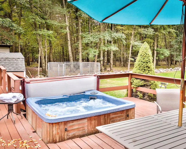 hot tub outside on porch of Honeymoon Lodge Cabins in the Poconos