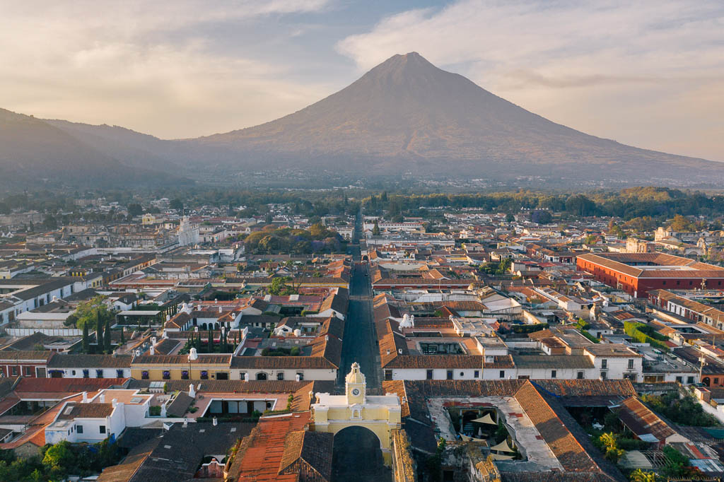 Areal photo of the historic old town of Antigua in Guatemala, surrounded by their active volcanos.