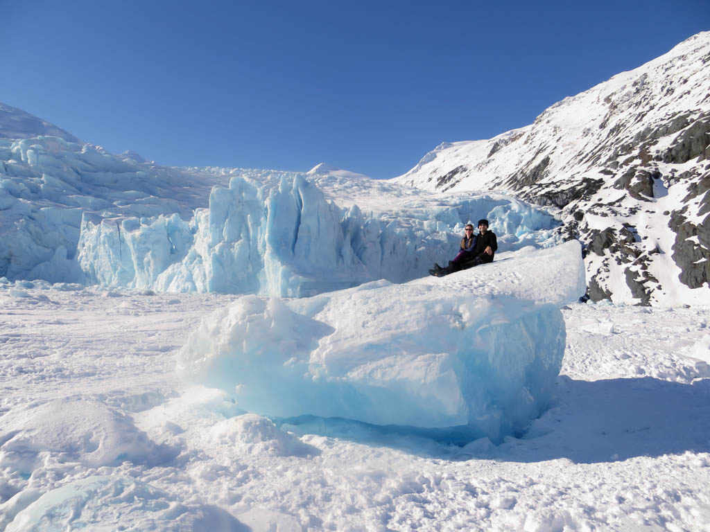 Two people sitting on top of an iceberg frozen in Portage lake with the Portage Glacier in the background. The shear size of the glacier & iceberg make the people look so tiny.