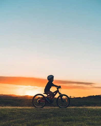 Kid enjoying outdoor on his bike during sunset in Auckland, New Zealand.