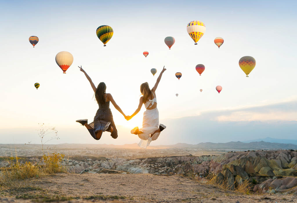 Girlfriends traveling and enjoying valley view at sunset in Cappadocia
