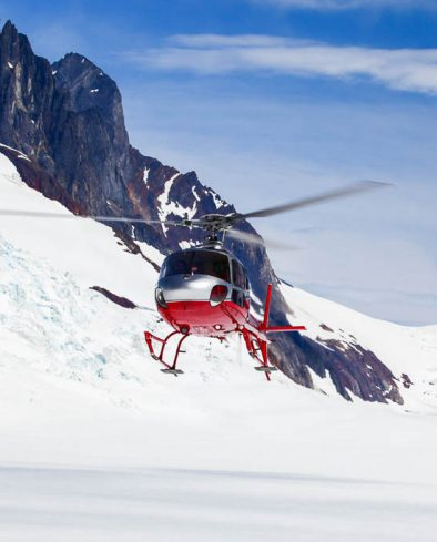 A helicopter landing on a remote mountain glacier.