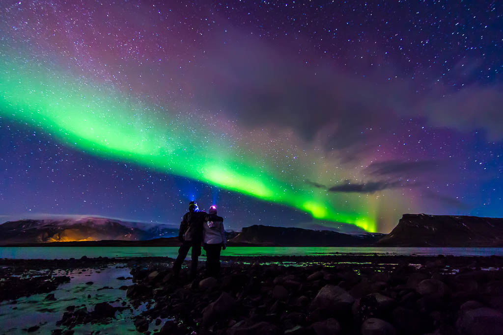 Young adventurist couple hugged while gazing in the dark night sky under the spectacular celestial lights Aurora Borealis, which makes Iceland popular spot for tourist willing to witness one of the greatest natural phenomenon. Shot with Canon EOS, wide angle lens, f2.8, long exposure.