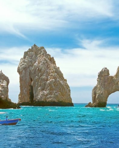 """Inside the bay at Cabo San Lucas, a small tourboat is dwarfed by rock formations including the famous """"El Arco."""""""