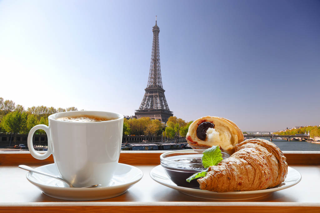 Cup of coffee with croissants and strawberry jam against Eiffel Tower in Paris, France