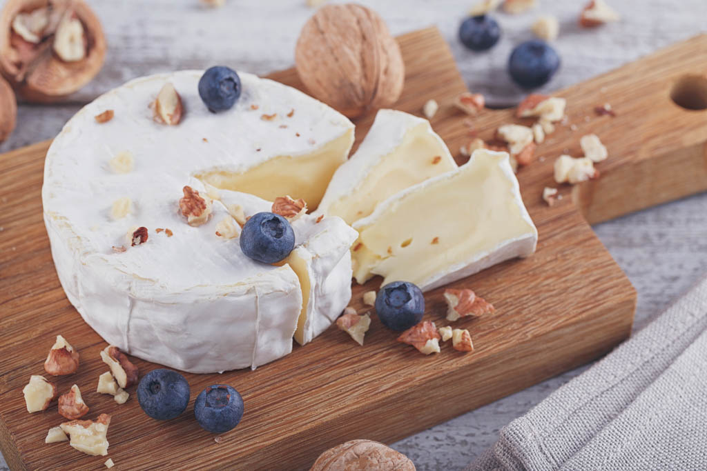 Soft french cheese of camembert served with chopped walnuts and blueberries on wooden plate.