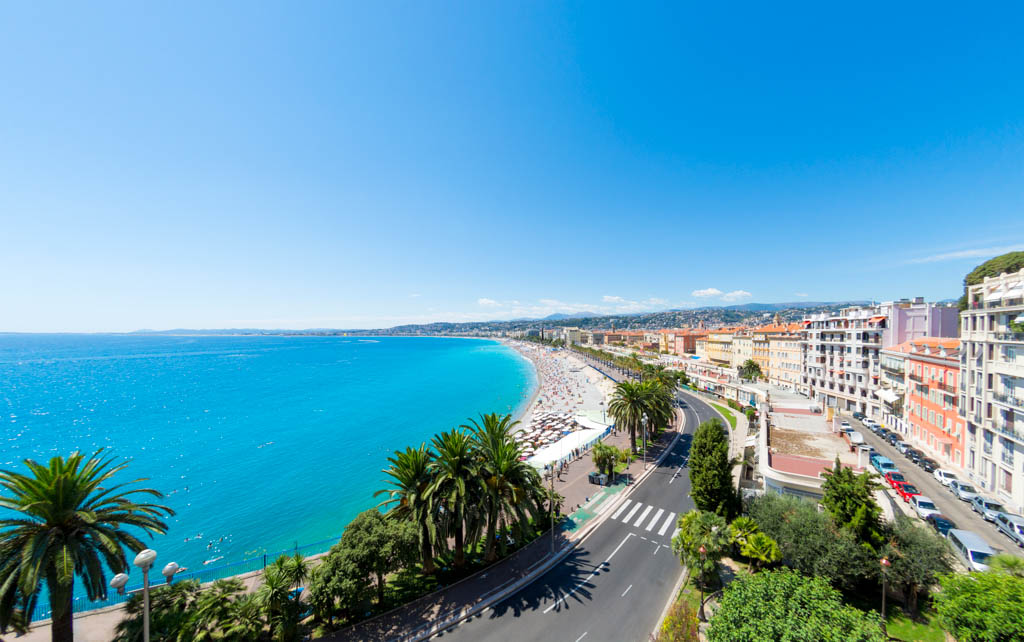 A view along the Promenade des Anglais and beach and seafront in Nice, France. Logos removed.
