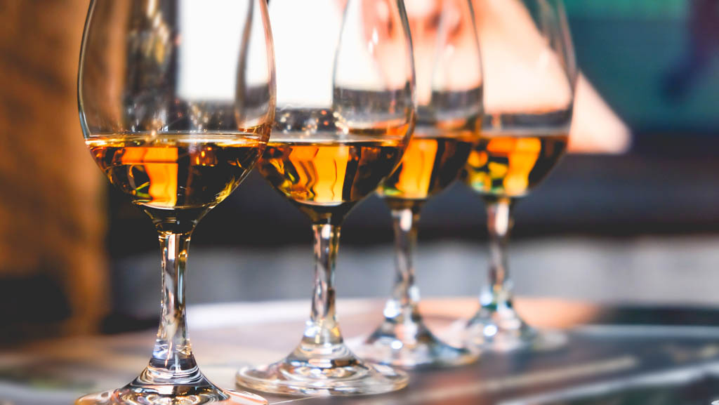 Close up glass of whiskey in a row