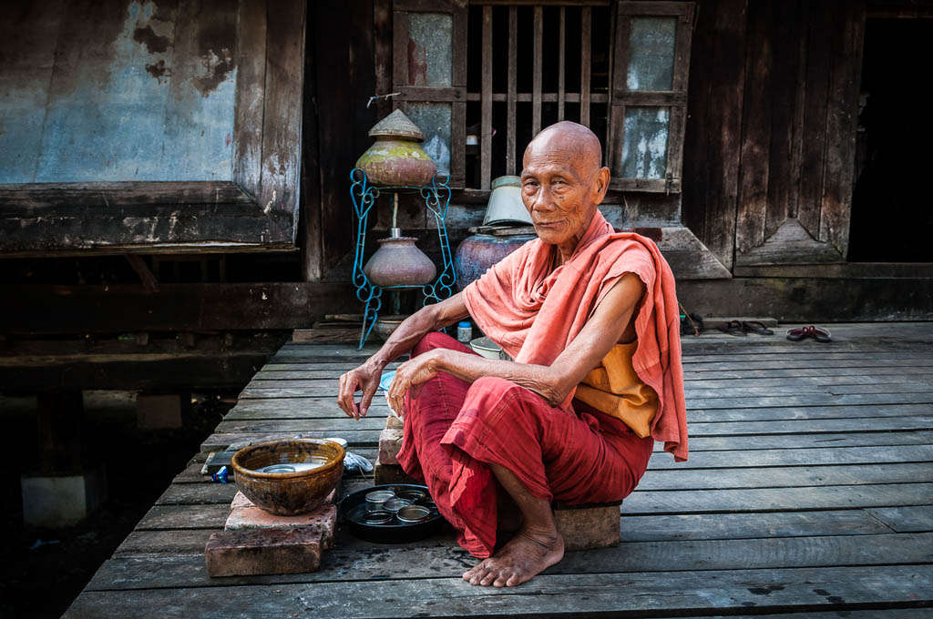 A Burmese monk in his 70s, sitting outside his monastery where he is washing dishes, in Mandalay, Myanmar