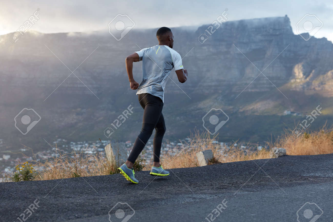 See new skin care routines for summer at tlc style. Back Shot Of Active Dark Skinned Man Being In Action Runs Across Mountain Road Leads Healthy Lifestyle Has Endurance And Motivation To Be Fit Poses Over Mountain Background Enjoys Nature Stock Photo