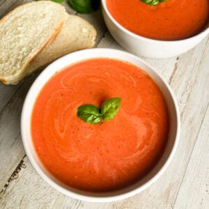 easy tomato basil soup in a white bowl with fresh basil and French bread for garnish