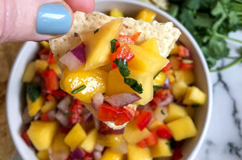 Mango salsa garnished with limes, cilantro, and served on a tortilla chip