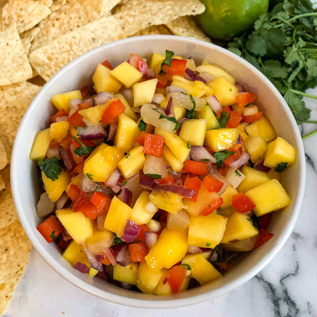 Mango salsa served with tortilla chips, and garnished with limes and cilantro