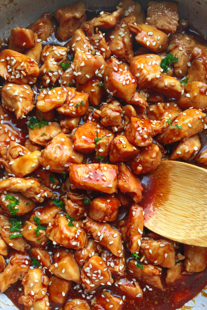 close up of Teriyaki Chicken Rice Bowl in a skillet with a wooden spoon for serving.