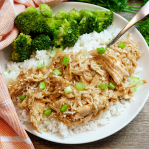 Instant pot honey garlic chicken over white rice on a white plate with a side of broccoli.