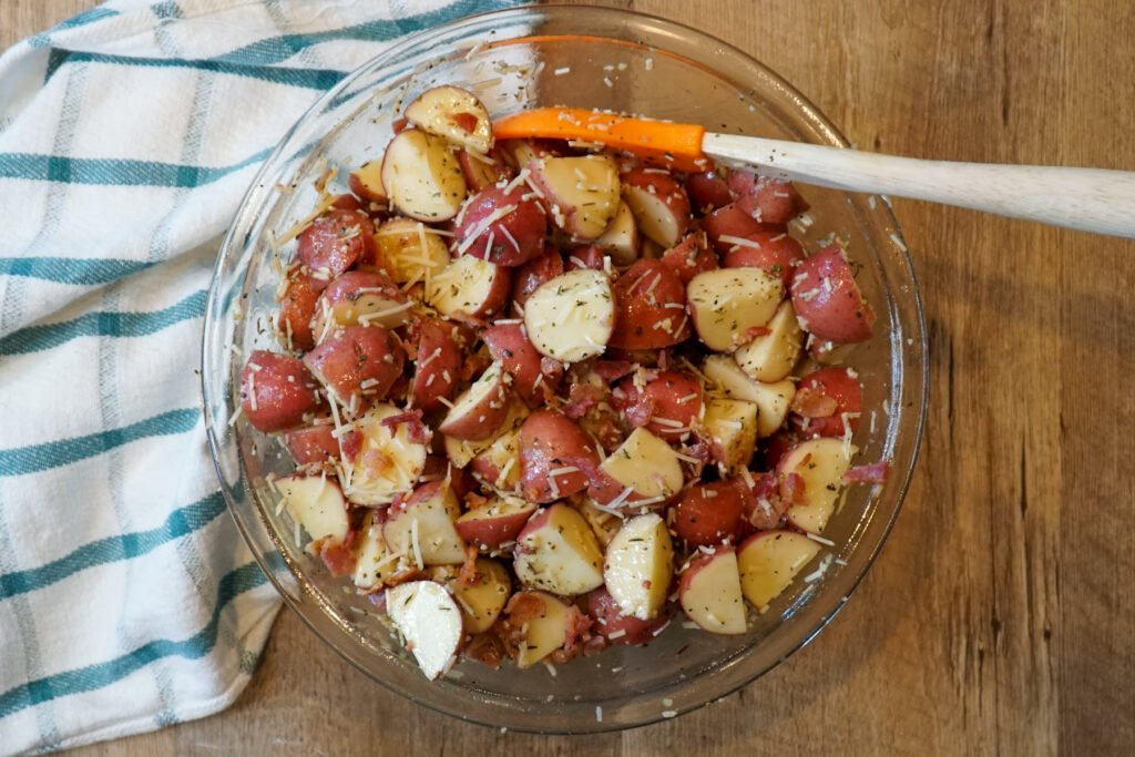 Red potatoes quartered and covered in olive oil, bacon, Parmesan cheese and spices in a large mixing bowl.