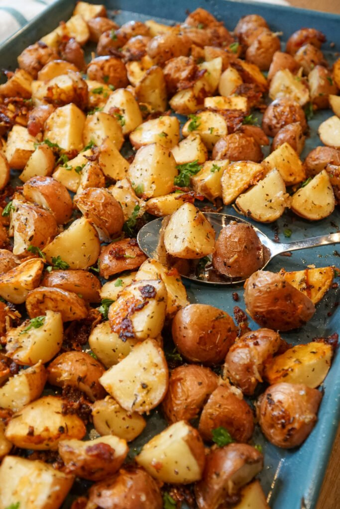 Close up of Parmesan garlic roasted potatoes garnished with bacon and fresh parsley on a baking tray.