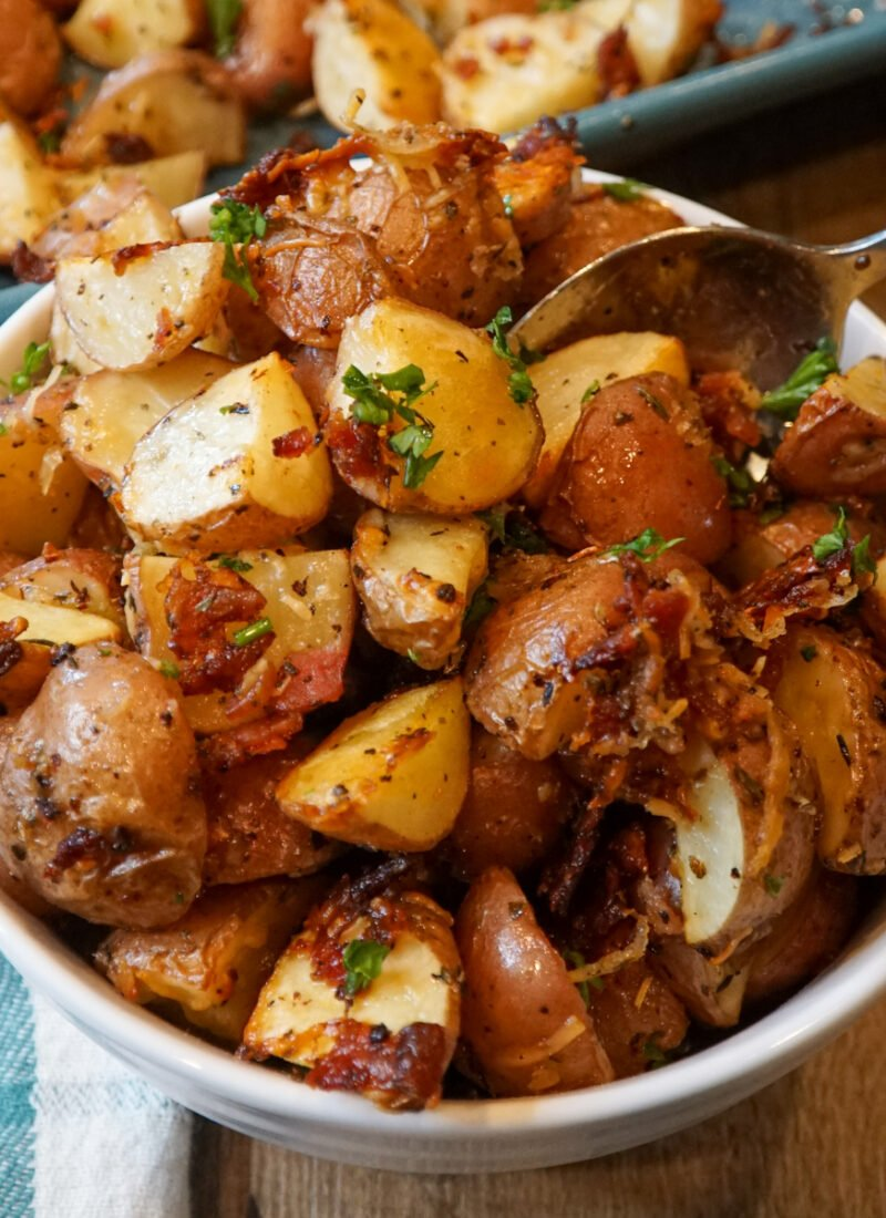 Close up of oven roasted potatoes with Parmesan cheese, bacon, and seasonings in a white bowl.