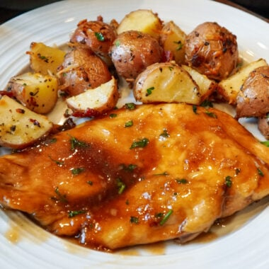Honey garlic chicken on a white plate with oven roasted Parmesan and bacon potatoes