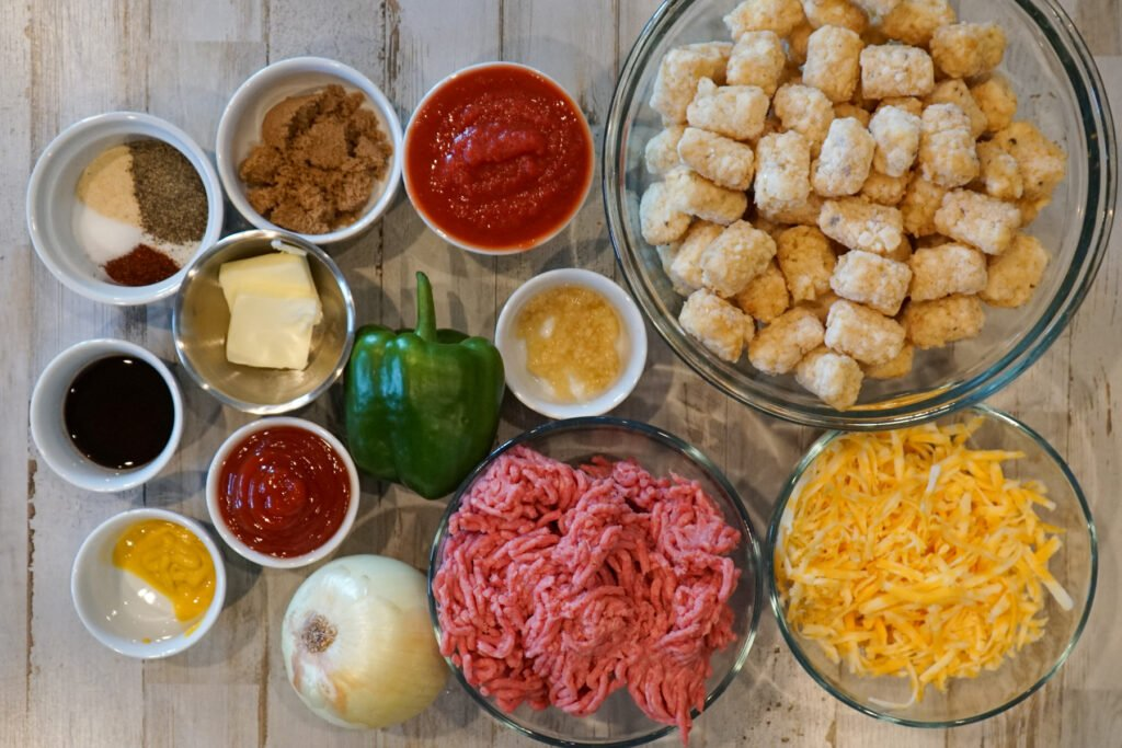 Ingredients for sloppy joe tater tot casserole frozen tater tots, ground beef, unsalted butter, green bell pepper, yellow onion, garlic cloves, tomato sauce, ketchup, brown sugar, yellow mustard, chili powder, Worcestershire sauce ,salt, ground black pepper, onion powder, cheddar cheese.