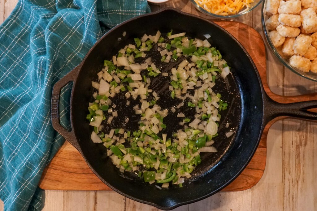 Onions and green peppers being sauteed in a cast-iron skillet.