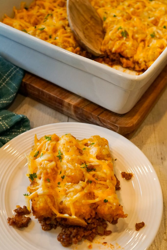 Sloppy Joe tater tot casserole on a while plate and in a white baking dish ready to be eaten.