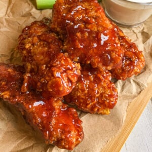 Honey BBQ Baked Chicken on a cutting board with celery sticks and ranch dipping sauce