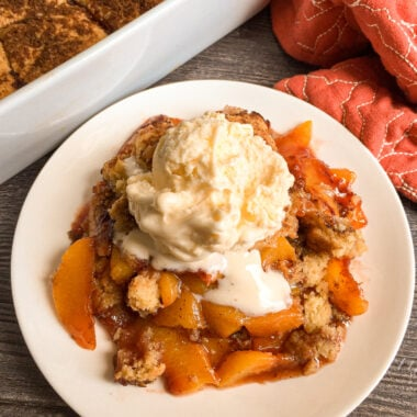 Warm peach cobbler on a white plate with a scoop of vanilla ice cream on top
