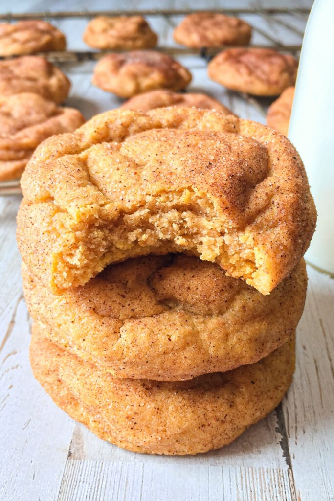 Close up shot of pumpkin snickerdoodle cookies stacked on top of each other with cookies in the background