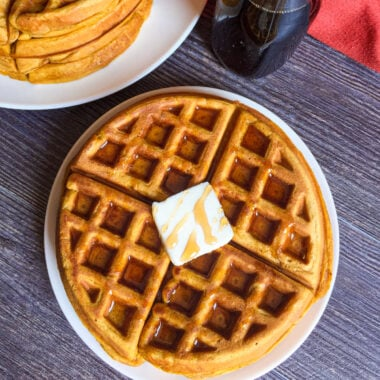 pumpkin waffle on a plate with butter and syrup drizzled on top