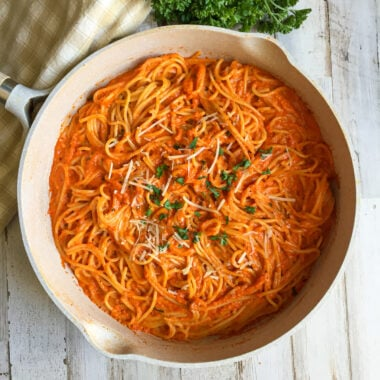 Roasted Red Pepper Pasta in a skillet topped with fresh parsley and fresh grated parmesan cheese