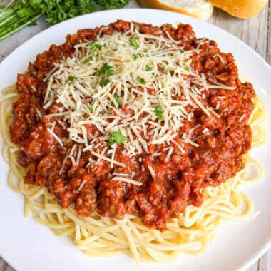 Homemade spaghetti sauce on a white plate with shredded parmesan cheese and fresh basil sprinkled on top