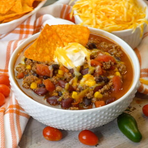 Best taco soup in a white bowl topped with shredded chees, sour cream and Doritos.
