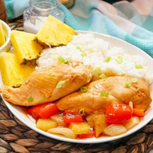 Close up of Hawaiian chicken in a Crock-Pot with slices of pineapple, red peppers, and onions.
