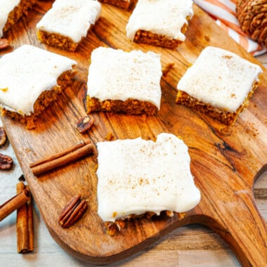 pumpkin bars with cream cheese filling cut into squares and placed on a cutting board with cinnamon sticks and pecans for garnish