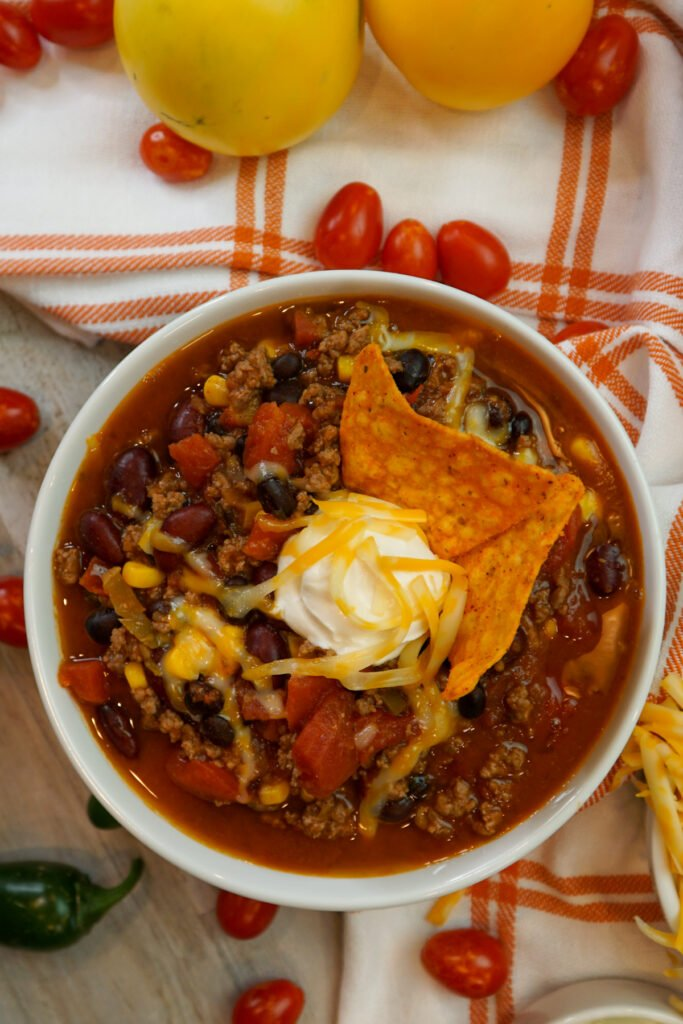 1 serving of taco soup in a white bowl surround by fresh tomatoes.