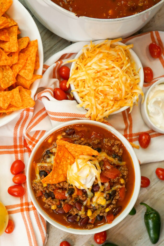 Homemade taco soup topped with cheddar cheese, sour cream, and Doritos in a white bowl.